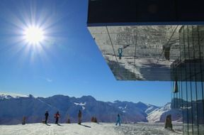 skiers in mountain landscape and glass facade of modern building, austria, sölden