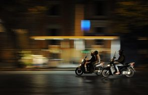 people riding scooters on night street