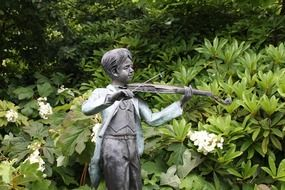 child boy playing violin, metal sculpture in park, australia, victoria, mount macedon
