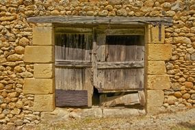 fragment of old barn, stone wall with wooden gate, france, dordogne