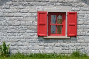 red wooden window with shutters on grey stone facade