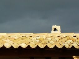old yellow tile roof under grey clouds