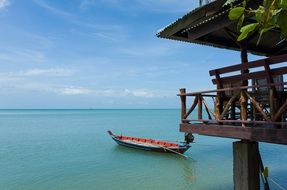 idyllic seascape with motor boat on calm blue water at wooden house, thailand
