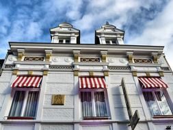 old facade with striped canopies on windows, netherlands, valkenburg