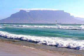 foamy sea waves splashing on beach in view of table mountain, south africa, cape town
