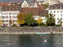 people resting rhine river embarkment at autumn, switzerland, basel
