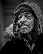 middle aged man in winter clothing with cigarette in lips, portrait