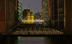 illuminated bridges above water at night, germany, hamburg, speicherstadt