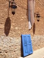 old street lanterns on wall above blue frame with shutters, spain, mallorca