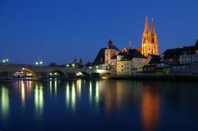 beautiful night cityscape with bridge, old town and cathedral, germany, regensburg