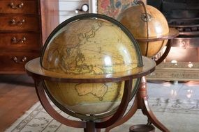 two antique wooden globes on map