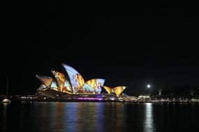 colorful illuminated sydney opera house on harbor at night, australia