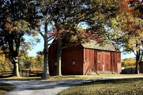 red wooden barn in countryside at autumn