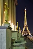 Gilded bronze statues in the central square of the Palais de Chaillot and eiffel tower at night, france, paris