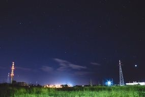 starry sky above meadow and distant city