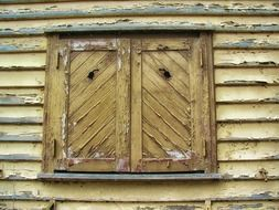 window with closed shutters on weathered wooden facade