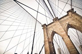 steel ropes of suspension brooklyn bridge at grey sky, usa, manhattan, new york city