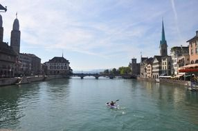 man in kayak on river in old city, switzerland, zürich