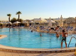 people resting at luxury swiming pool, malta, intercontinental hotel