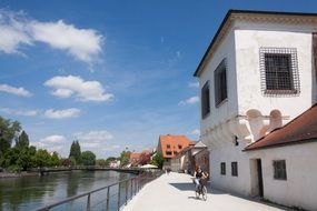 woman riding bicycle on waterfront, germany, landshut