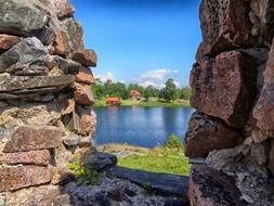 view of red houses on green coast through stone ruin, sweden