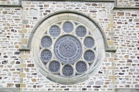 rosette window on wild stone church facade
