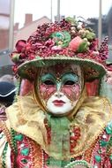 masked person in hat, decorated with fruits and berries, on carnival, italy, venice