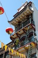chinese building with lanterns and flags on lines across street, usa, california, san francisco