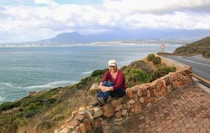 caucasian woman sits on stone fence at scenery coast, south africa, cape town