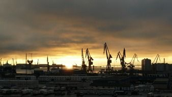 harbor in dusk and cranes at sunset sky, spain, canary islands, las palmas