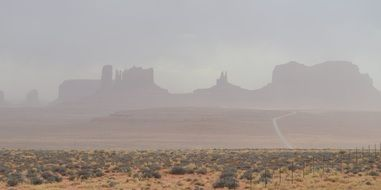 rock formations through dust cloud in air at storm, usa, utah, monument valley