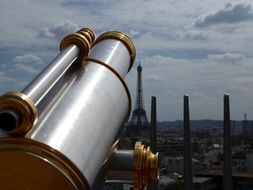 vintage binoculars at distant view of eiffel tower in cityscape, france, paris