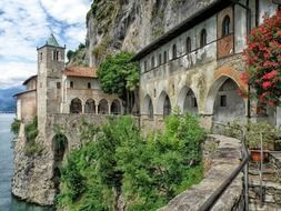 passage at facade of santa caterina del sasso monastery on rock, italy