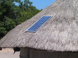 solar panel on straw roof of tribal hut