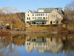 winchester public library building mirroring on calm water at fall, usa, massachusetts