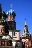 colorful domes of st basil's cathedral and kremlin tower at sky, russia, moscow