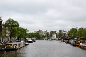 embankment with boats at pier in old town, netherlands, amsterdam