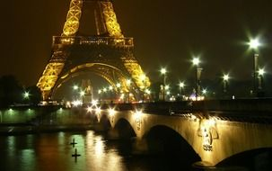 illuminated bridge across siene river at eiffel tower at night, france, paris