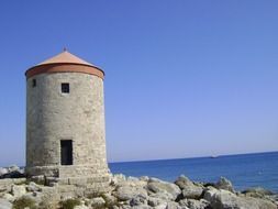 old flour mill on rocky coast at blue sea, greece, rhodes