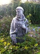 saint francis with bird, stone statue in garden