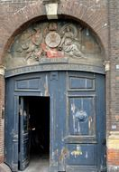 old doorway with lettering and carved figures atop door, denmark, copenhagen