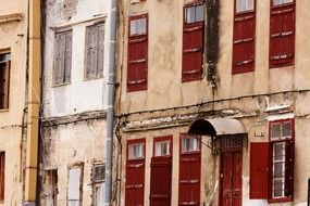 old facade with red shutters at windows, greece