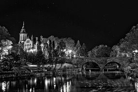 church at river and bridge above water at night