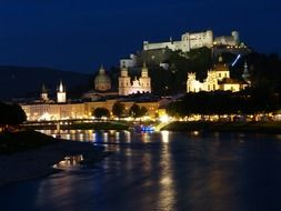 View from the water to the historical part of Salzburg at night