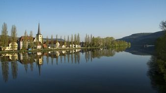 houses and church mirroring on water at spring countryside