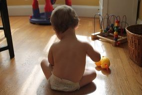 baby plays toys on floor, back view