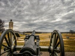 oldtime cannon on battlefield under clouds, usa, pennsylvania, gettysburg