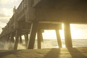 waves splashing on breakwater under wooden pier