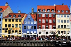 crowd of people on waterfront at corful old buildings, denmark, copenhagen