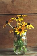 water glass jar yellow flowers wood backgraund